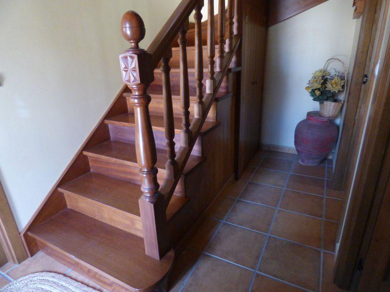 escalera completa en madera de iroko primer tramo con peldaos cerrados con y aprovechado de esa parte baja para una pequea despensa
